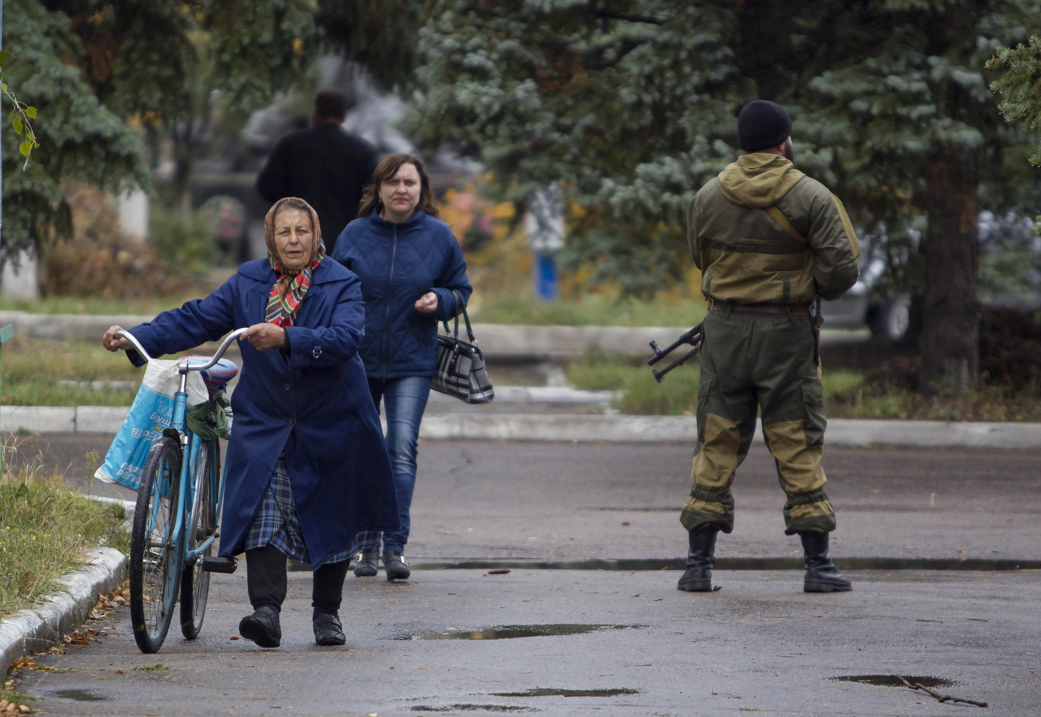 Residents walk past a pro-Russian rebel in the southern coastal town of Novoazovsk