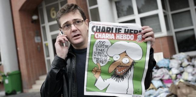 Charb-directeur-de-la-publication-de-Charlie-Hebdo-montre-lexemplaire-du-2-novembre-devant-les-locaux-frappés-par-un-attentat-à-Paris