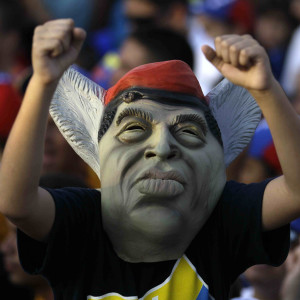A supporter of opposition presidential candidate Henrique Capriles wears a mask representing Venezuela's President Hugo Chavez during Capriles' closing campaign rally in Barquisimeto, Venezuela, Thursday, Oct. 4, 2012. Capriles will run against Chavez in the presidential elections Oct. 7. (AP Photo/Fernando Llano)