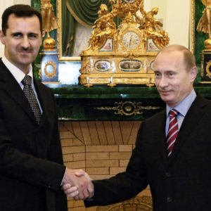 FILE  In this Tuesday, Dec. 19, 2006 file photo Vladimir Putin, then Russian President, right, and his Syrian counterpart Bashar Assad smile as they shake hands in Moscow's Kremlin. Russia defied international efforts to end a crackdown on civilians by Assad regime, shielding it from the United Nations sanctions and providing it with weapons. (AP photo/RIA Novosti, Mikhail Klimentyev, Presidential Press service, file)