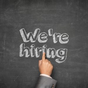 We are hiring concept on black blackboard with businessman hand