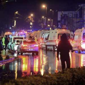 Medics and security officials work at the scene after an attack at a popular nightclub in Istanbul, early Sunday, Jan. 1, 2017. Turkey's state-run news agency says an armed assailant has opened fire at a nightclub in Istanbul during New Year's celebrations, wounding several people.(IHA via AP)