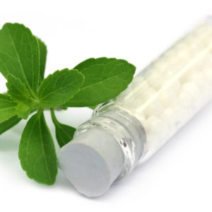 Homeopathic globules with stevia over white background