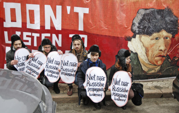 Feb. 5, 2016 - Kiev, Ukraine - Ukrainian activists holds symbolic ears with inscriptions ''Do not listen to Russian propaganda!'' in different languages,in front of a banner featuring Vincent Van Gogh's self-portrait with the cut off ear,during their performance near the Netherlands Embassy in Kiev. The activists called upon Netherlands to not trust Russian propaganda against Ukraine ahead of a referendum on an association agreement of the Ukraine with EU, which will take place in the Netherlands on 06 April 2016. The slogans include ''Better to cut one's ear, than to listen to Russian propaganda'' and ''Netherlands is a friend of Ukraine.' (Credit Image: Global Look Press via ZUMA Press)