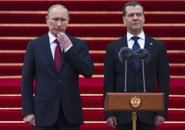 """Russian President Vladimir Putin and former President Dmitry Medvedev, right,  stand as an honor guard march during an inauguration ceremony at the Cathedral Square in the Kremlin in Moscow,  Russia, Monday, May 7, 2012. Vladimir Putin took the oath of office for a third term as Russia's president on Monday, saying he considers """"service to the fatherland and our nation to be the meaning of my life."""" (AP Photo/Alexander Zemlianichenko, pool)"""