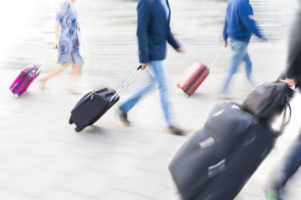 Bunch of people with suitcases in blurred motion