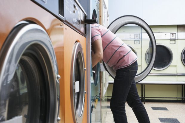 Young man taking clothes from dryer, side view Royalty free: For comercial usage price on demand