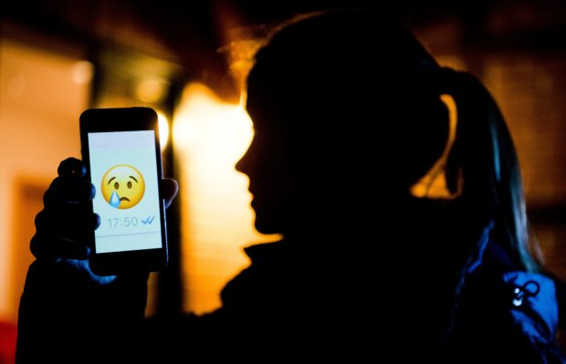 """ILLUSTRATION - A young girl shows the display of a smartphone with a crying emoji within the messenger """"WhatsApp"""" in Hanover, Germany, 4 February 2017. The official term for spreading false information or insulting people is """"Cybermobbing""""The 7 February is Safer Internet Day with a focus on Cybermobbing.   (Staged Scene) Photo: Julian Stratenschulte/dpa"""